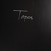 The word 'tapas' written on a black surface