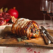 Rolled stuffed roast pork on a chopping board