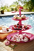 A tiered cake stand holding individual cakes and treats by a swimming pool