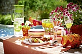 A table laid for a meal with lemonade, fruit and salad by a swimming pool