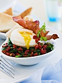 Poached egg with crispy bacon on a bed of spinach salad with sundried tomatoes