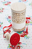 A jar containing dry ingredients for making wholemeal oat biscuits, with a stamp