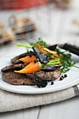 Beef fillet with glazed carrots and black garlic