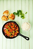 Spicy turkey goulash in the pan with rice and bread rolls