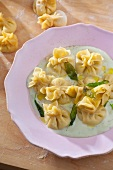 Fiocchi (filled dumplings) with Gorgonzola and pear filling, on herb sauce