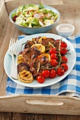 Grilled pork collar steaks with grilled vegetables and salad