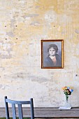 Portrait of child on unpainted wall above wooden table