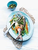 Gilt-head bream with pesto on a bed of vegetables
