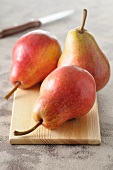 Three red pears on a small wooden board