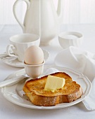 Toast with butter and a boiled egg on a breakfast table