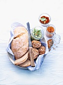 White bread and seeded bread rolls in a bread basket, with various spreads