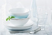 Stacked dinner bowls and plated, drinking glasses and forks