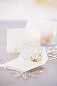 Envelopes of gold and silver sequins as table decorations