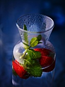 A carafe of water with strawberries and mint