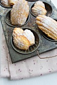 Madeleines in an antique baking tray on a floral napkin