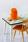 Small stack of sliced raw carrots on miniature chopping board with dolls' house furniture