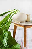 Small white radish with leaves on dolls' house table