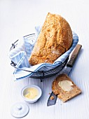 Yoghurt and sesame seed bread in a bread basket, with butter