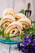 Cheese and ham rolls with egg salad and violets