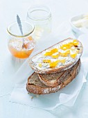 Mixed rye and wheat bread, topped with butter and orange jam