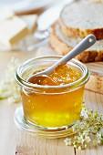 A jar of elderflower jelly with a spoon