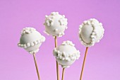Vanilla cake pops with white icing against a purple background