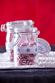 Red and white peppermint sweets in storage jars for Christmas