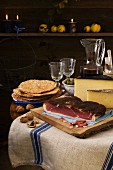 A rustic light meal from South Tyrol, consisting of dry-cured ham, Schüttelbrot (crispy unleavened bread), nuts, cheese and wine