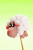 A cake pop decorated to look like a sheep