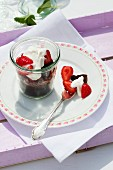 Chocolate pudding in a jar with strawberries and cream