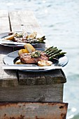 Grilled lamb steaks with asparagus on the landing stage