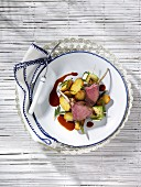 Saddle of lamb with fried potatoes and courgette rolls
