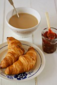 Two croissants, berry jam and a bowl of latte for breakfast