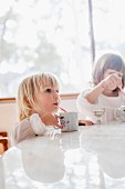 Two girls sitting at the breakfast table and drinking through straws