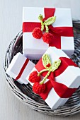 Small gift boxes decorated with red ribbons and crocheted cherries