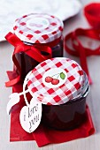 Jars of cherry jam decorated with cherry stickers and bows