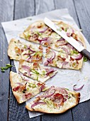 Tarte flambée with onions, spring onions and bacon