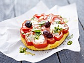 Mini pizza topped with beef tomato, olives and pesto