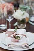 A white place setting decorated with a bow and herbs