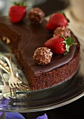 A fine chocolate cake made with cranberries and chocolate ganache and decorated with strawberries and nut pralines