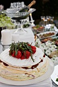 Camembert cake with tomato peppers and rosemary on a buffet table