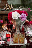 Various cut glasses and a bunch of flowers on a table at a garden party