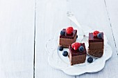 Cubes of chocolate cheesecake with raspberries and blueberries
