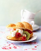 A croissant filled with fruits and cream