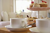 Cup of tea & pastries on cake stand on table in living room (close-up)