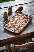 Pear clafoutis in the baking dish on a wooden table