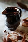 Melted chocolate in and on a dark ceramic jug