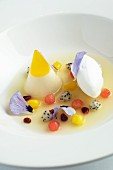 Exotic fruit salad with a quenelle of quark and pansies