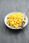 Diced squash on a plate with a knife
