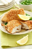 Breaded chicken escalope with butter, lemon wedges and peas